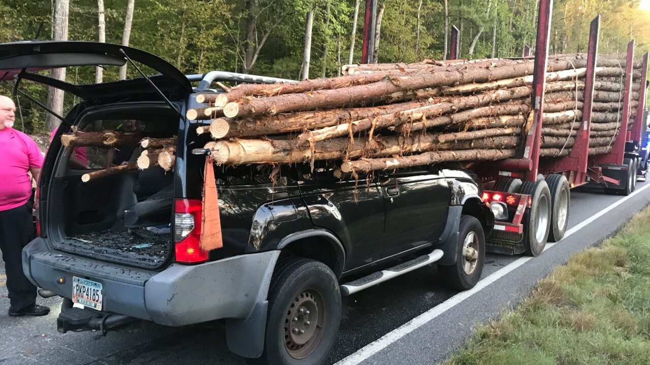 Driver rescued alive after vehicle is impaled by logs from truck