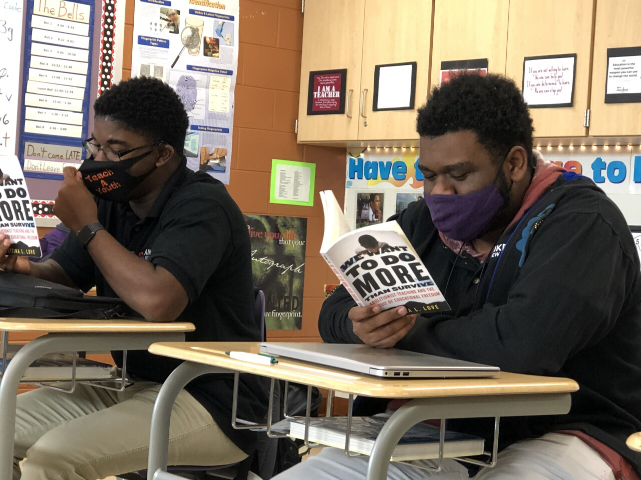 Two Aiken High School students read in preparation for their book club with Keith LaMar. Both students have short, dark hair and are wearing masks.