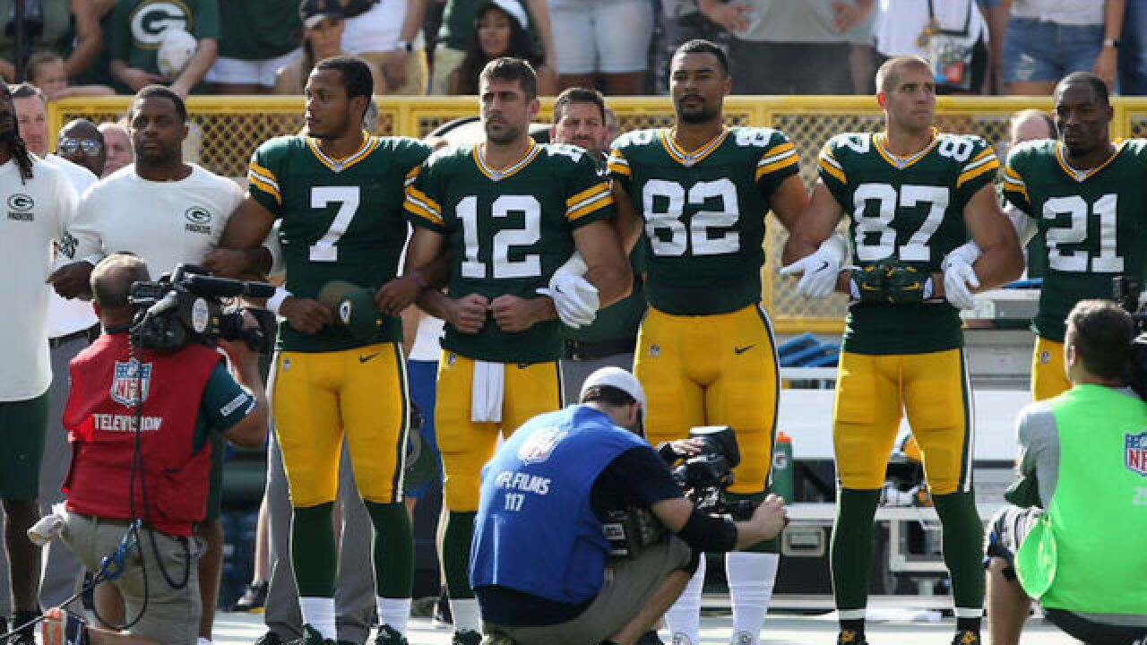Green Bay Packers players lock arms in unity; fans opt out of unity display