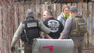 U.S. Marshals with the Fugitive Task Force escorted a man in handcuffs out of the house.
