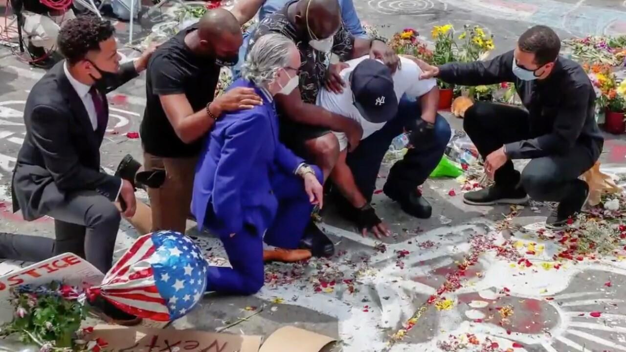 Shane Harris kneeling with George Floyd's family in Minneapolis