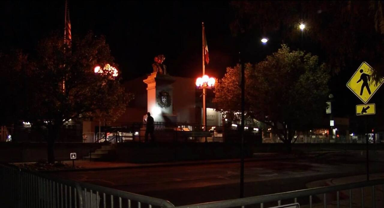 Pueblo police officers shining their flashlights on the Christopher Columbus statue on Sunday morning