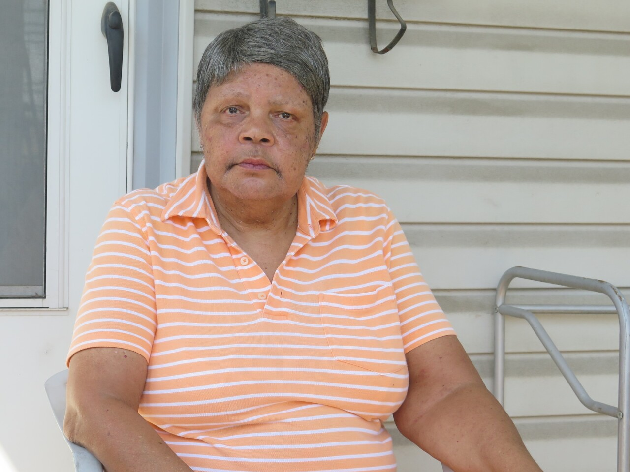 Pat Herndon poses on the porch of her Covington home. She is wearing a pale orange top with white stripes and has short grey hair.