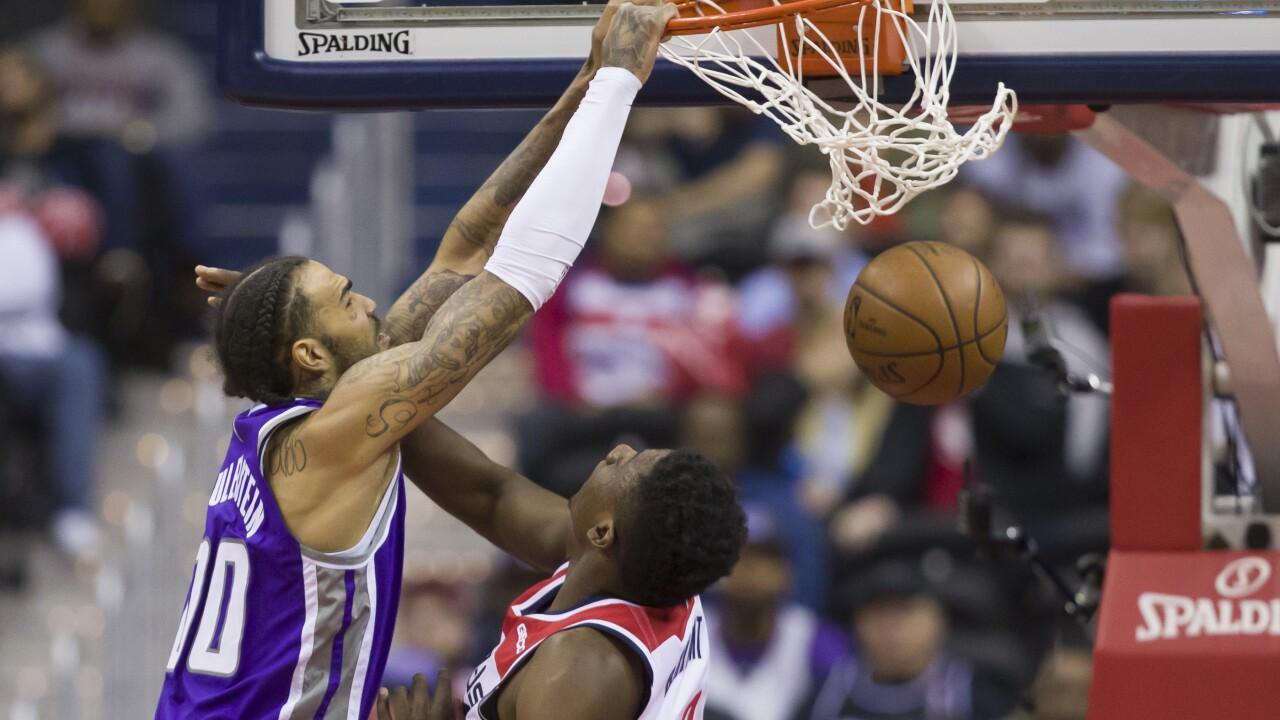 Sacramento Kings center Willie Cauley-Stein (00) dunks past Washington Wizards center Thomas Bryant (13) during the second half of an NBA basketball game Monday, March 11, 2019, in Washington. (AP Photo/Alex Brandon)