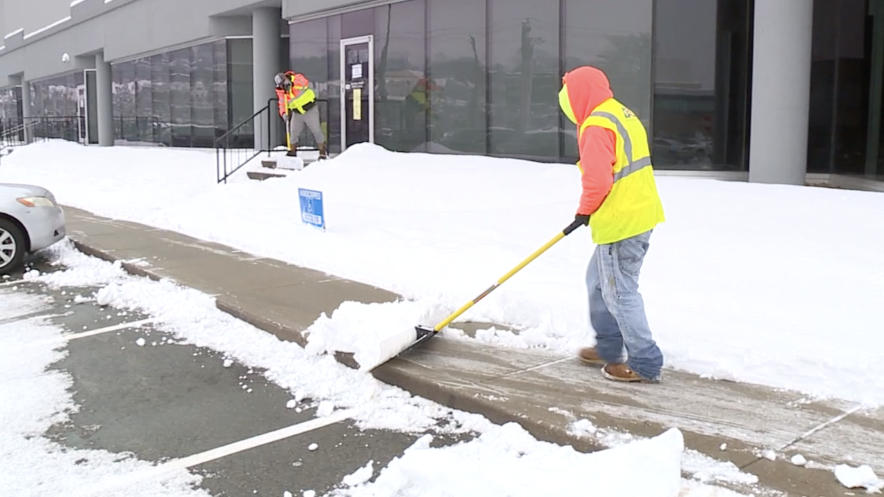 Workers clear snow outside a Hamilton County vaccine provider, Feb. 9, 2021.