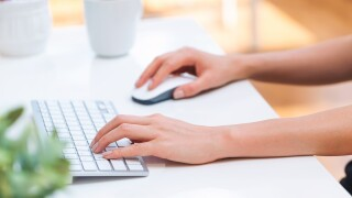 Person typing on her office computer