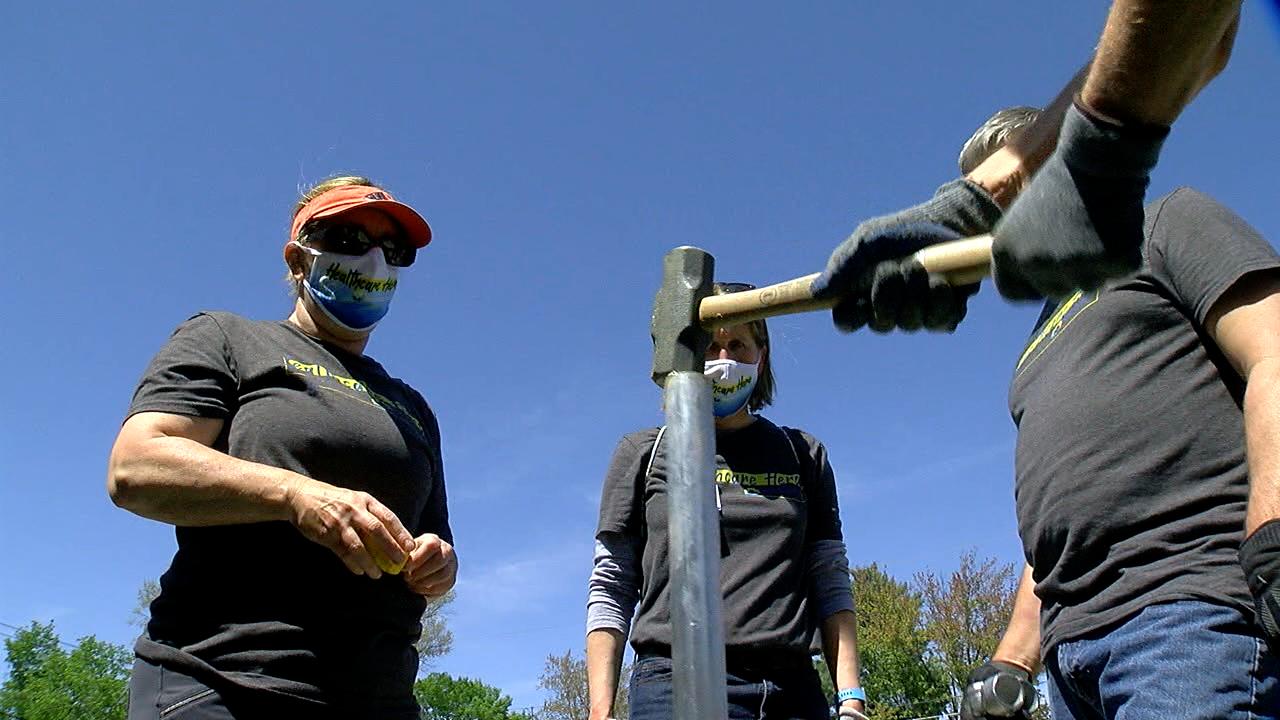 People Working Cooperatively Volunteers sink a fencepost