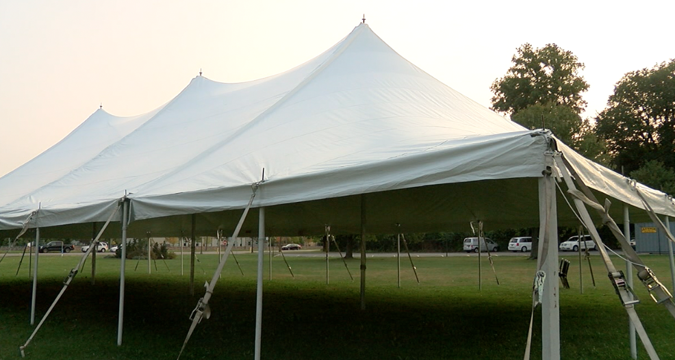 Students stand in circles under this tent and play their instruments