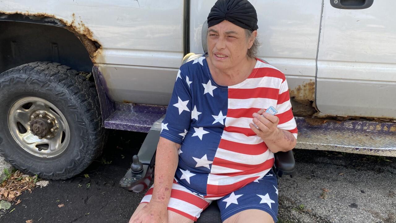 Milwaukee resident Darcy Buddnauertz sitting holding her inhaler up