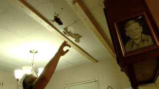 Dale Mitchell pointing at a hole in his ceiling