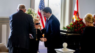 Gov. Ron DeSantis helps Ann Bowden into her seat as husband lies in honor at old Florida Capitol, Aug. 13, 2021