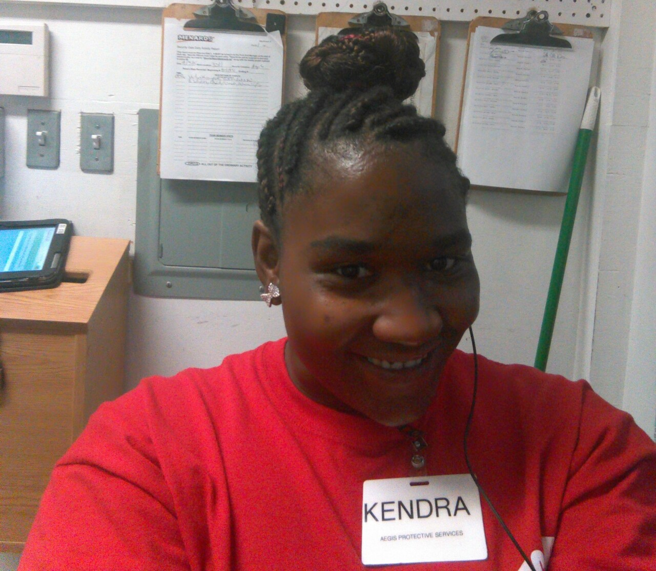 Kendra Davis smiles in this undated photo taken while she was at work. Her braided hair is wrapped in a bun atop her head, and she's wearing a red shirt.
