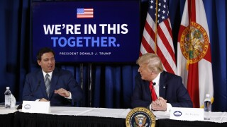 President Donald Trump speaks with Florida Gov. Ron DeSantis during a roundtable discussion on the coronavirus outbreak and storm preparedness, July 31, 2020, at Pelican Golf Club in Belleair, Fla.