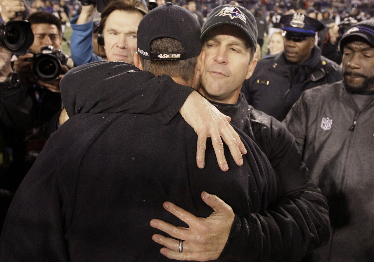 Baltimore Ravens head coach John Harbaugh hugs San Francisco 49ers head coach Jim Harbaugh after Thanksgiving game in 2011