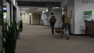 People are walking to the baggage claim to get their belongings.