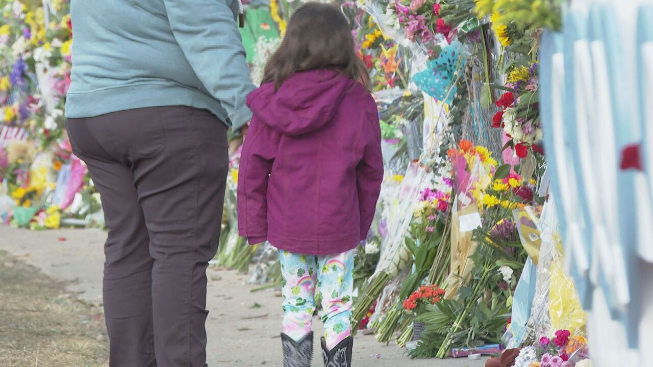 Young girl looks at Boulder shooting memorial