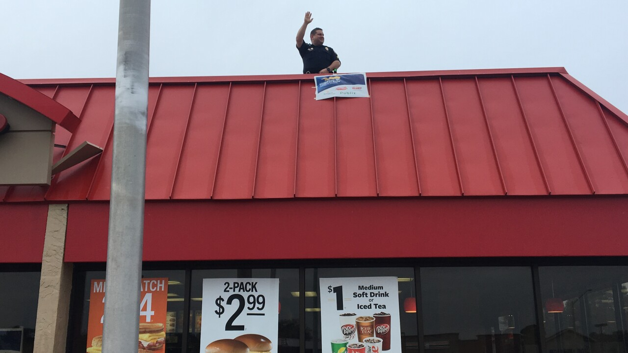 'Cop-on-Top': Local police officer stands on top of Virginia Beach Hardee's for SpecialOlympics