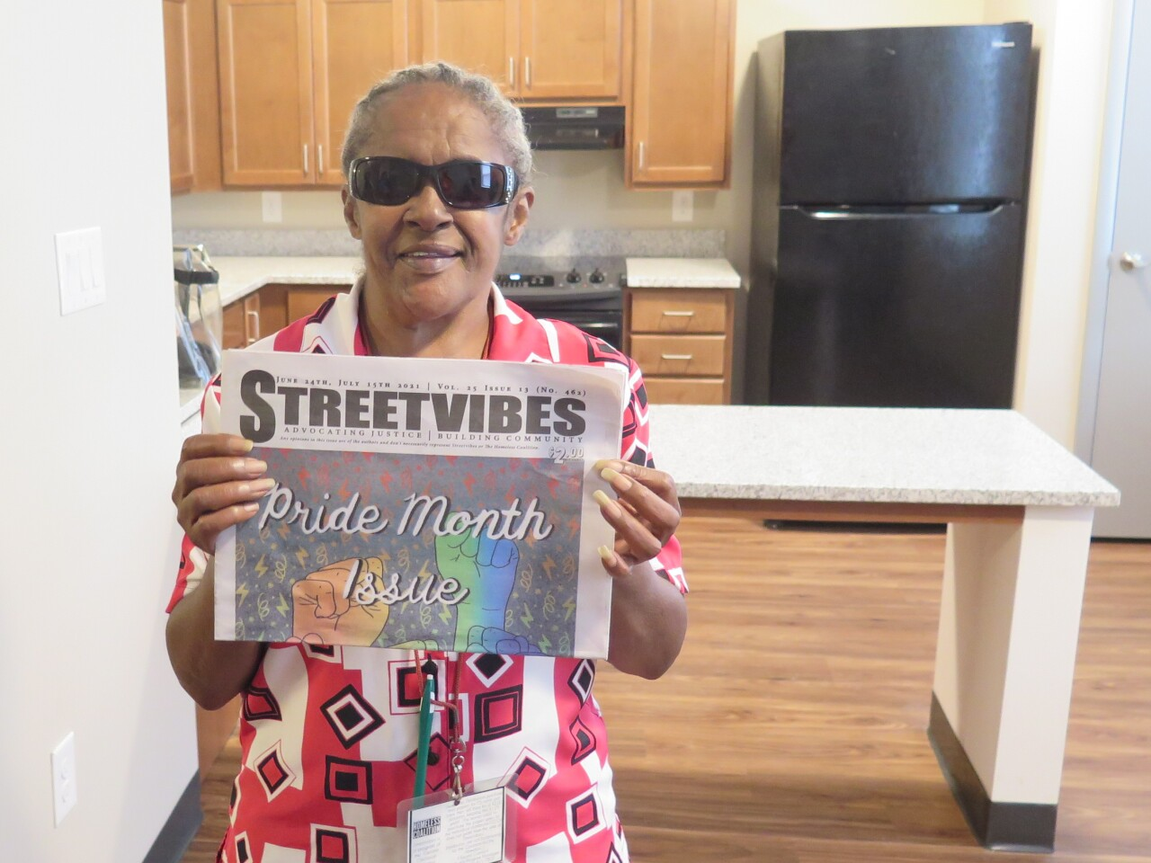 Willa Jones poses with a copy of the Streetvibes newspaper she sells. She's standing in one of the newly renovated Logan Towers apartments. The kitchen's wooden cabinets and new appliances are in the background.