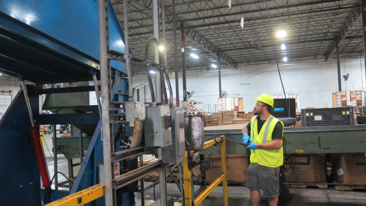 Adam Criss operates a large machine at Close the Loop, a company that breaks down plastics and other materials so they can be reused in other products. Criss is wearing a hard hat and safety vest in the photo.