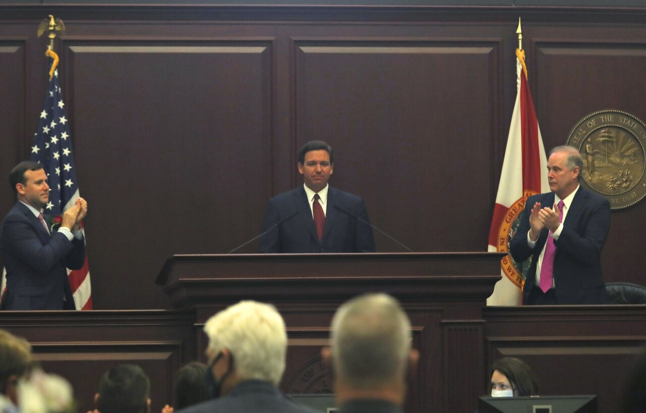 Gov. Ron DeSantis receives applause from House Speaker Rep. Chris Sprowls and Senate President Wilton Simpson in Tallahassee, March 2, 2021