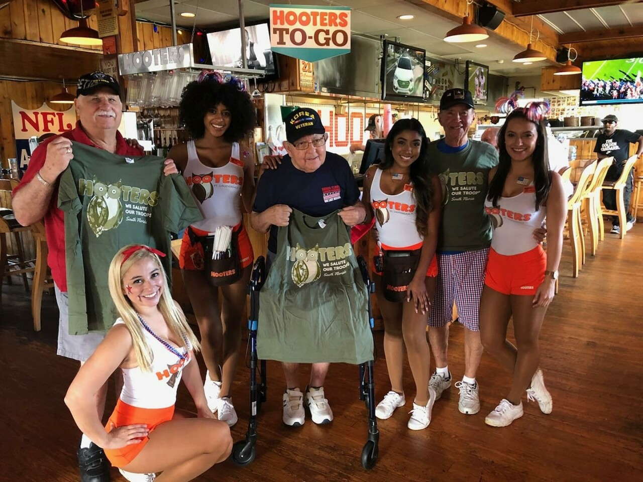 Hooters girls with veterans holding 'We Salute Our Troops' shirts