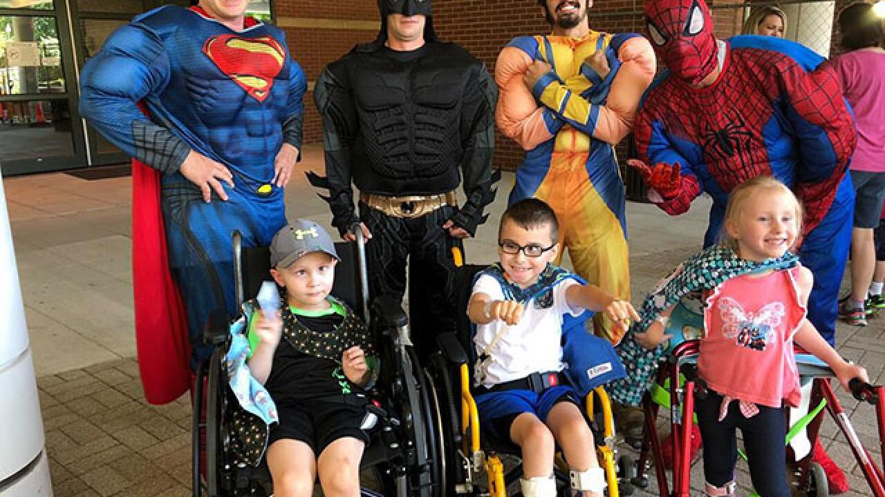 Superheroes wash windows at Akron kids hospital