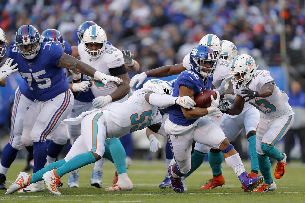 New York Giants running back Saquon Barkley runs through Miami Dolphins defense in 2019
