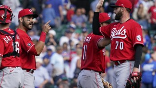 Cincinnati Reds relief pitcher Tejay Antone, right, celebrates with teammates Eugenio Suarez, second from left, and Kyle Farmer after they defeated the Chicago Cubs in a baseball game in Chicago, Sunday, May 30, 2021.