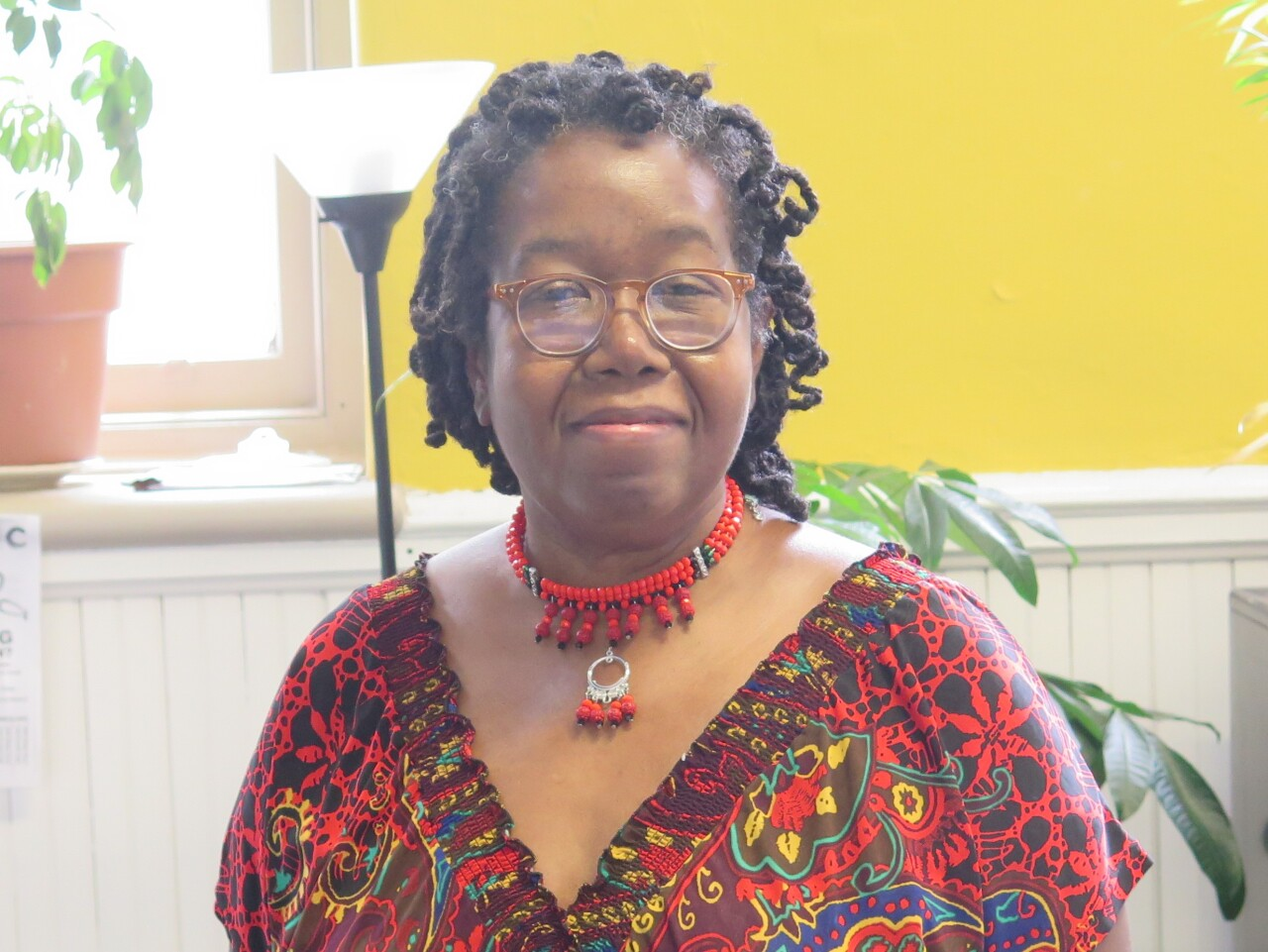 This portrait of Cynthia Ford was taken in June of 2020. Ford is wearing glasses, a red necklace and a red printed top.