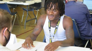 Devontae Johnson does a practice interview at a Cincinnati Works workshop and resource fair in East Westwood on Aug. 17, 2021. He is wearing a white tank top and a Pittsburgh Steelers lanyard.