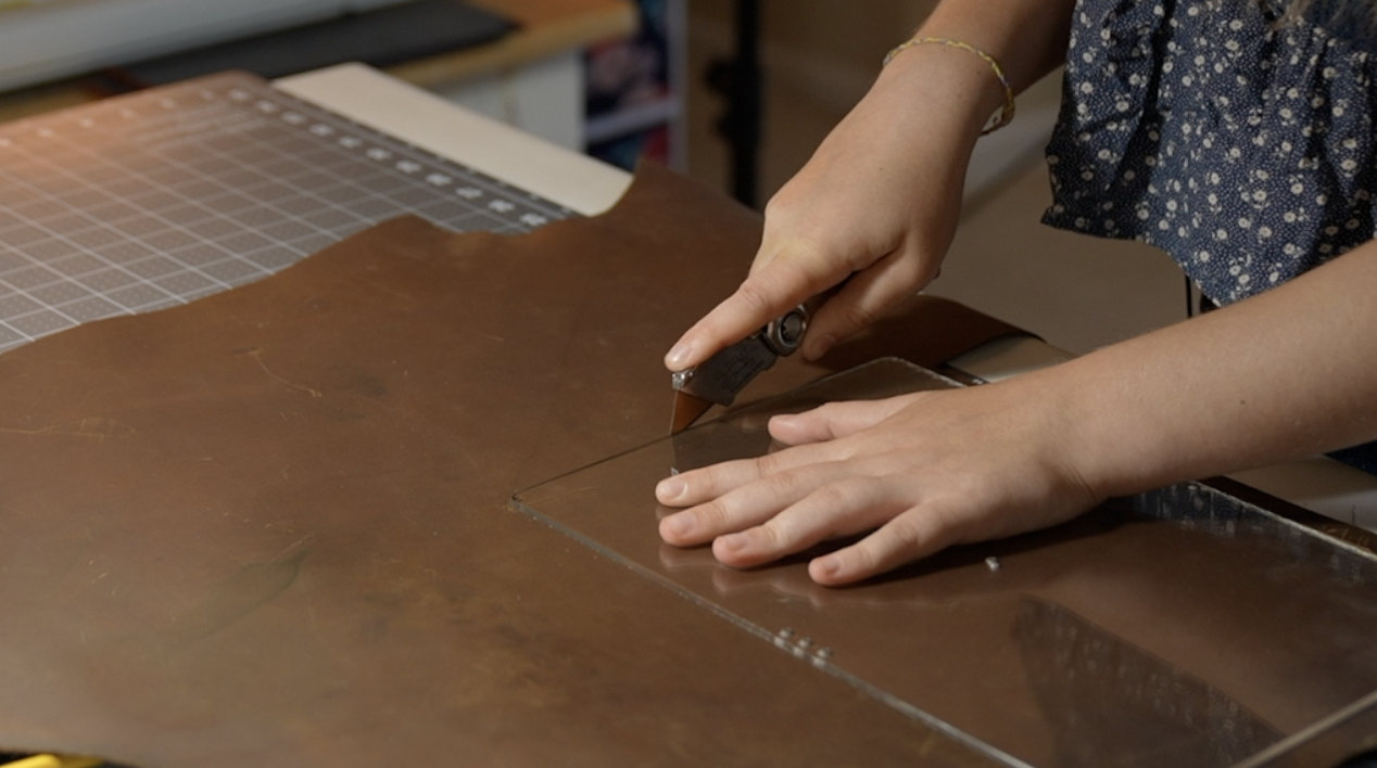 Evelyn cutting the leather using a template she made