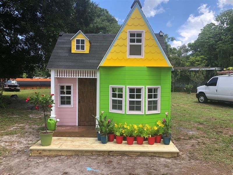 A pink, green, and yellow playhouse with a porch and flowers