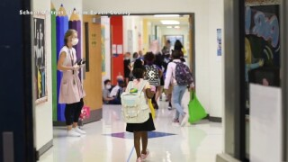Students wearing face masks fill the hallway of a Palm Beach County school during the 2020-21 academic year.jpg