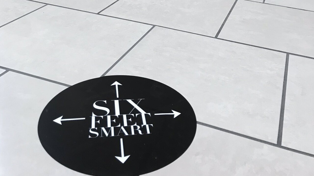 A sign on the floor at the Gardens Mall emphasizes customers to stay 6 feet apart.