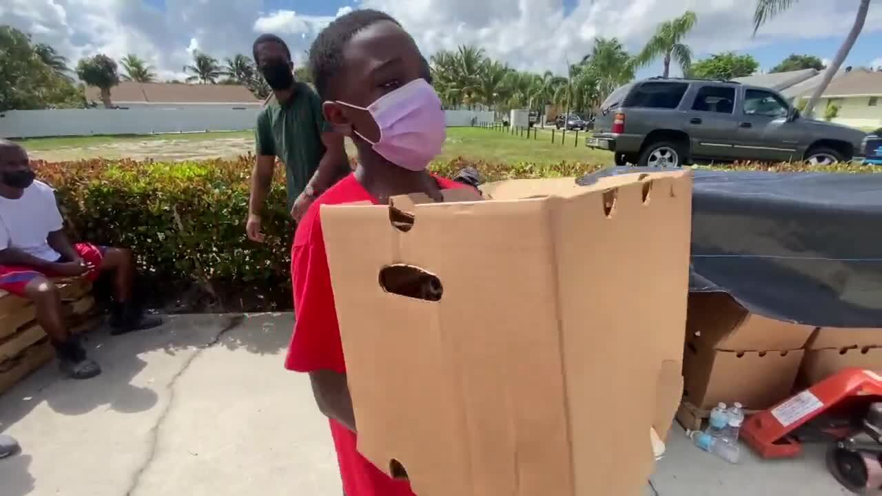 Boy hands out box of food in Lake Worth Beach to those in need
