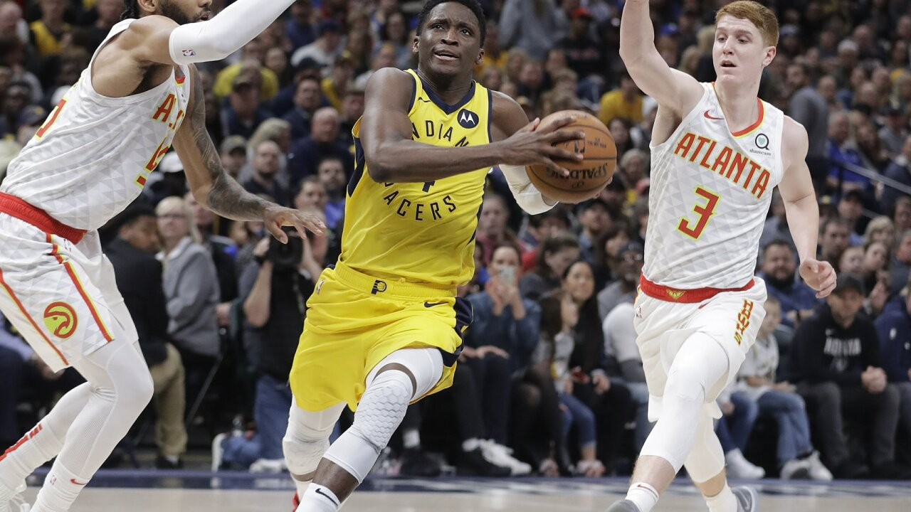 Indiana Pacers' Victor Oladipo (4) goes to the basket against Atlanta Hawks' DeAndre' Bembry (95) and Kevin Huerter (3) during the second half of an NBA basketball game, Monday, Dec. 31, 2018, in Indianapolis. Indiana won 116-108. (AP Photo/Darron Cummings)