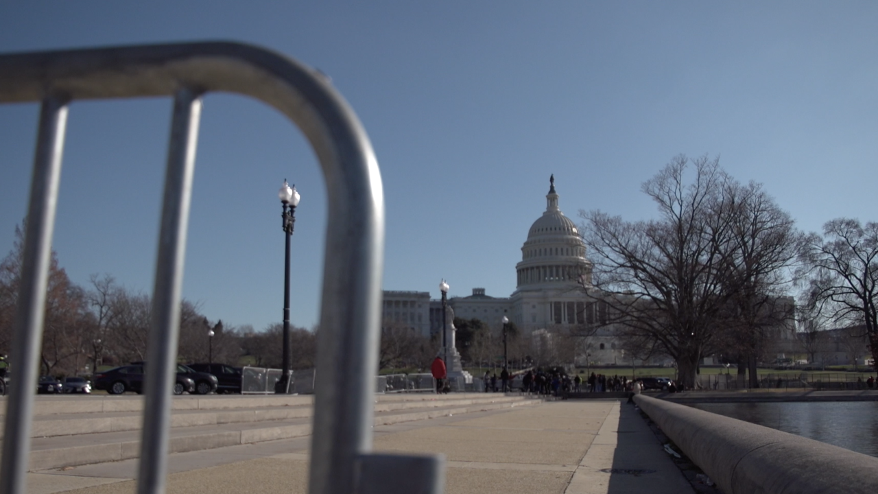 The exterior of the U.S. Capitol is seen beyond a barrier, a day after rioters, with seemingly little pushback from law enforcement, managed to storm into the building.
