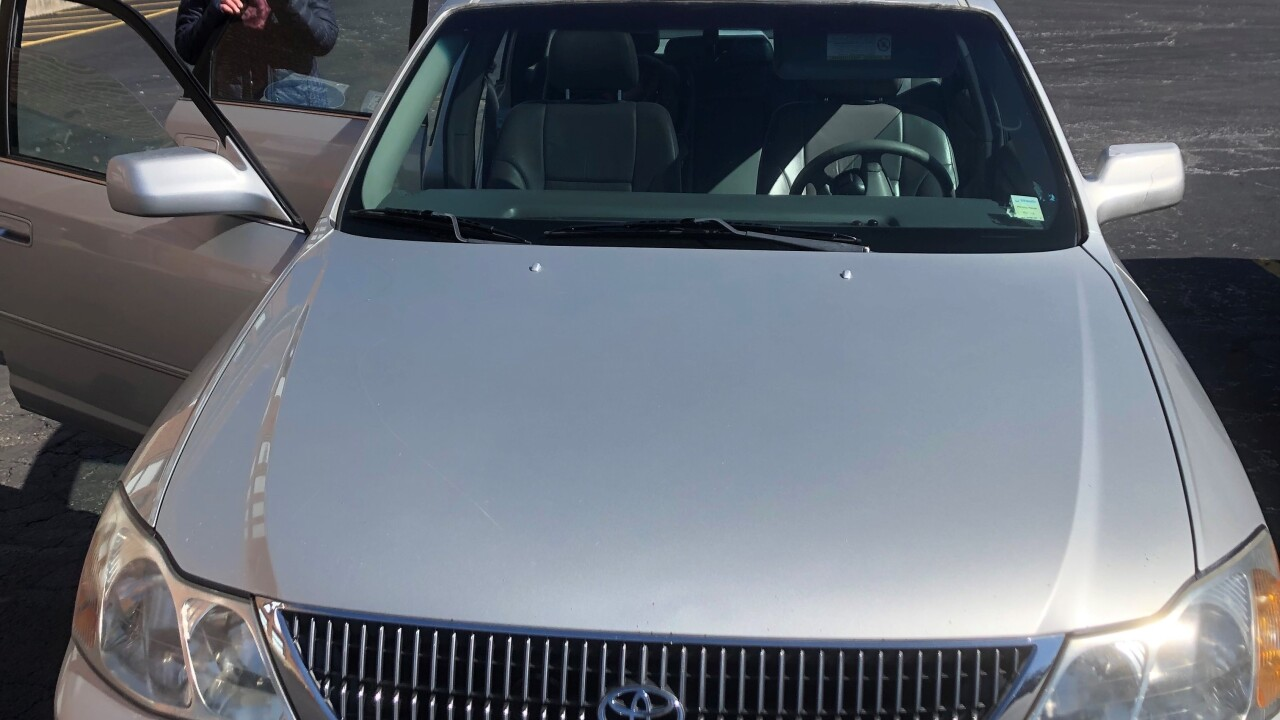 A woman stands near an open back door of a silver 2000 Toyota Avalon that she received from Samaritan Car Care Clinic. The woman's face is blurred to protect her privacy.