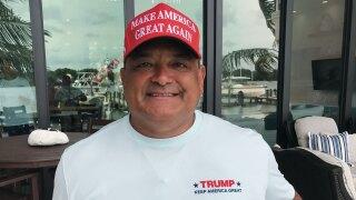 Trump Boat Parade organizer Carlos Gavida smiles as his 'Trump' boat reflects in the glass behind him.