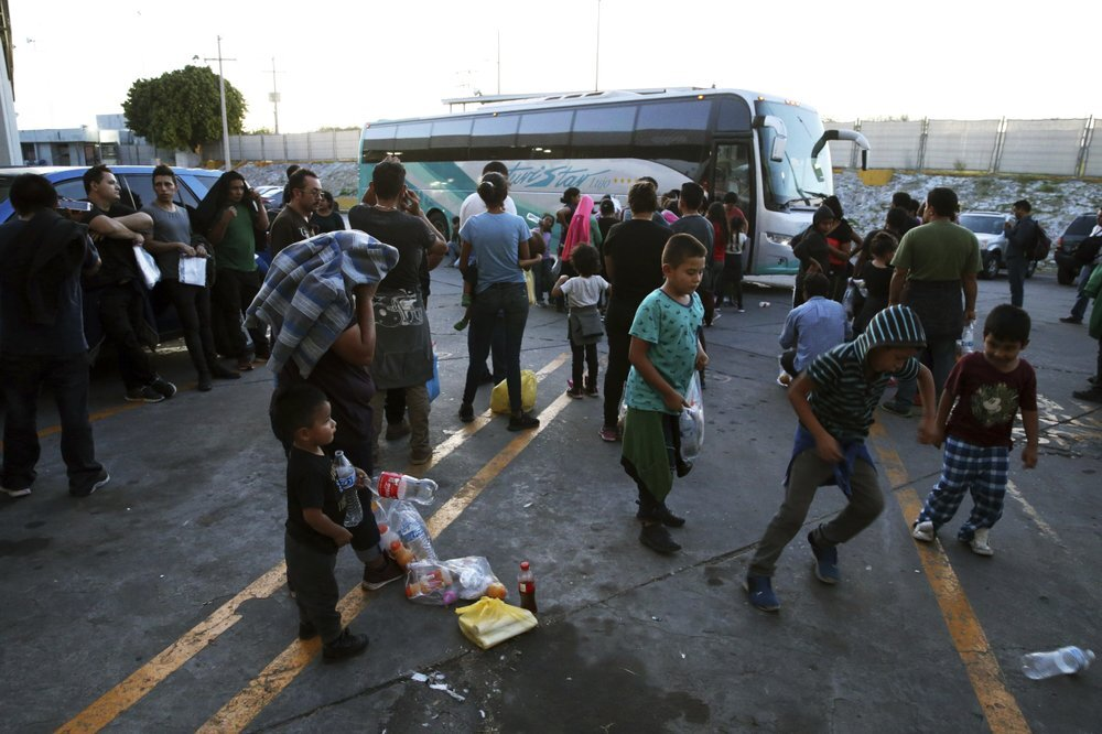 In this July 16, 2019 photo, migrants wait outside at an immigration center on the International Bridge 1, to be bused from Nuevo Laredo to Monterrey Mexico. The migrants went willingly knowing the dangers that lurk in Tamaulipas, where organized crime groups have been known to extort, kidnap and kill people like them. (AP Photo/Marc