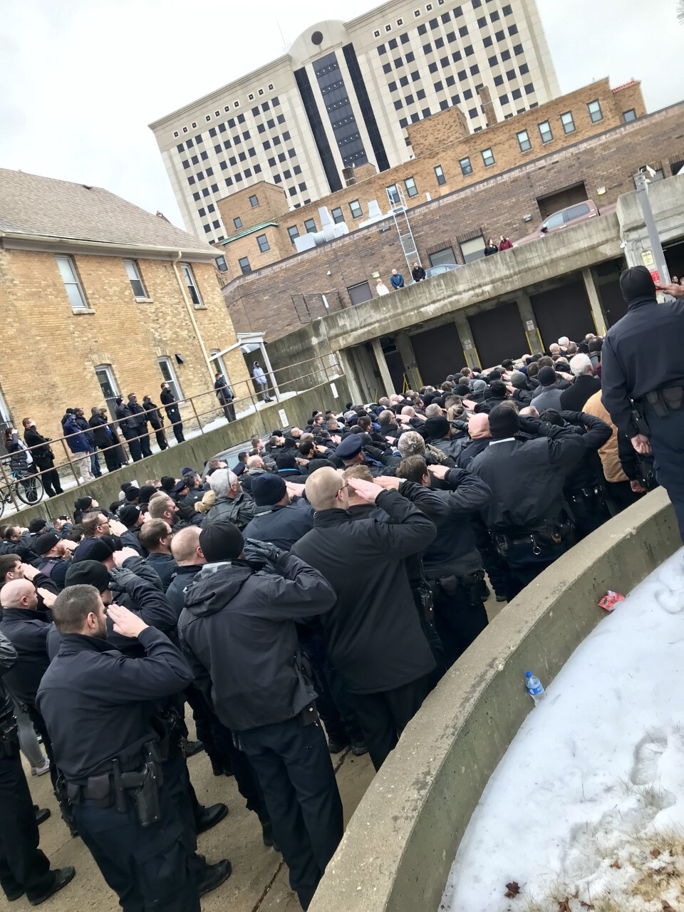 Officers salute as the procession for the fallen MPD officer ends outside the Medical Examiner's Office.