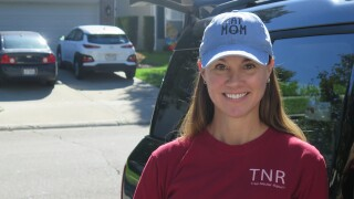 """Melanie Dial is smiling in this picture. She has long, dark blonde hair, and she's wearing a light blue """"Cat mom"""" baseball hat and a dark red t-shirt that says TNR below her left shoulder."""