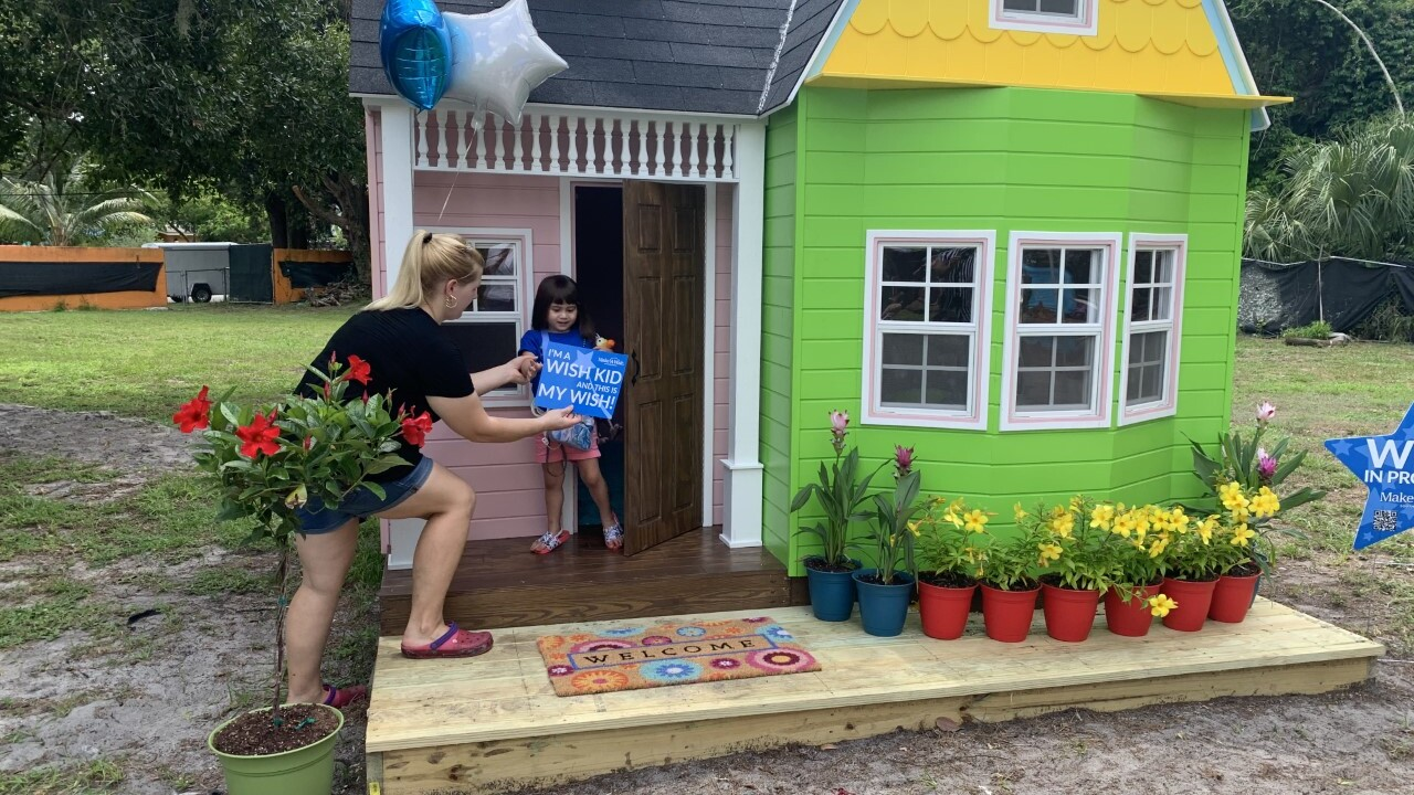 Little girl holding a sign given to her by her mother in front of a pink, green, and yellow playhouse with a porch and flowers.