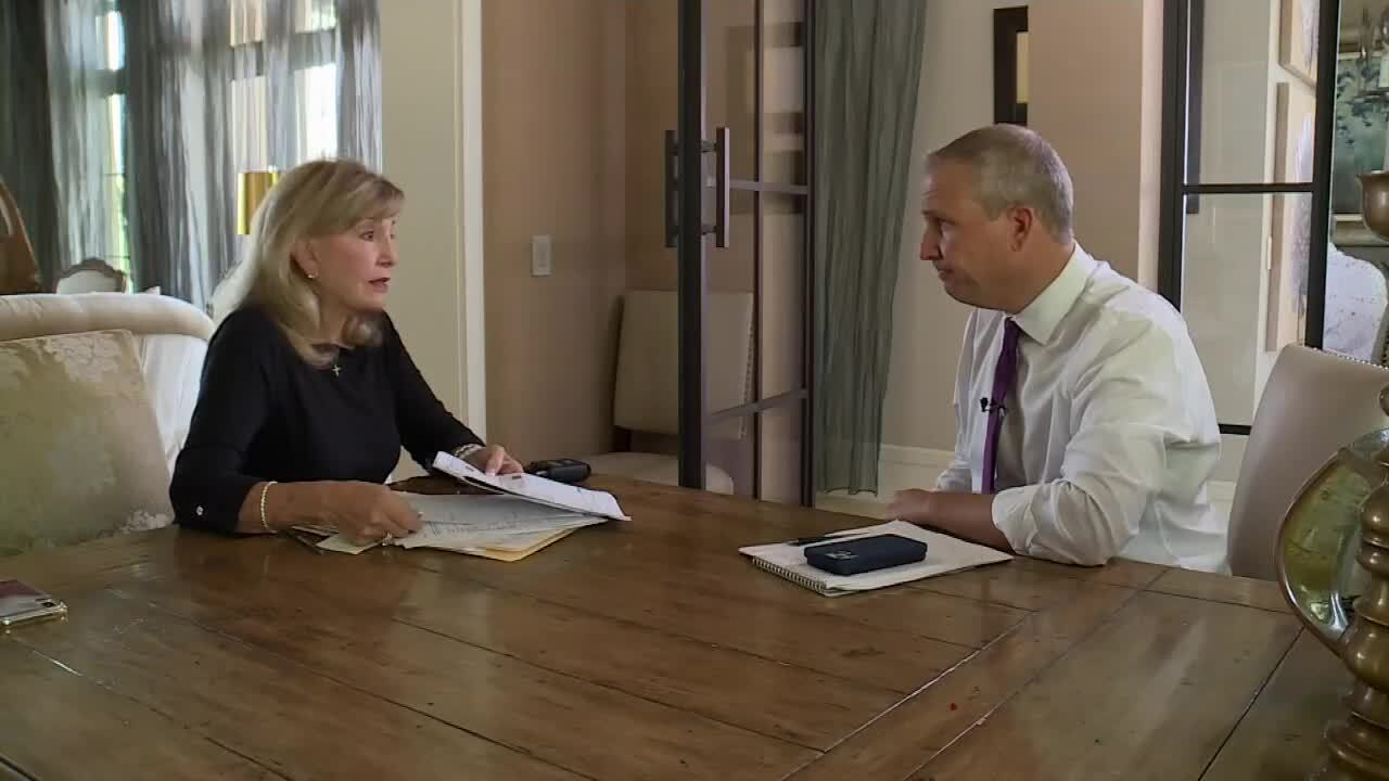 Linda Polly shows Michael Buczyner puzzling water bills from Delray Beach