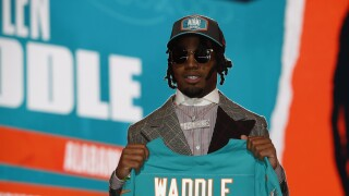 Jaylen Waddle holds Miami Dolphins jersey on stage during first round of 2021 NFL Draft