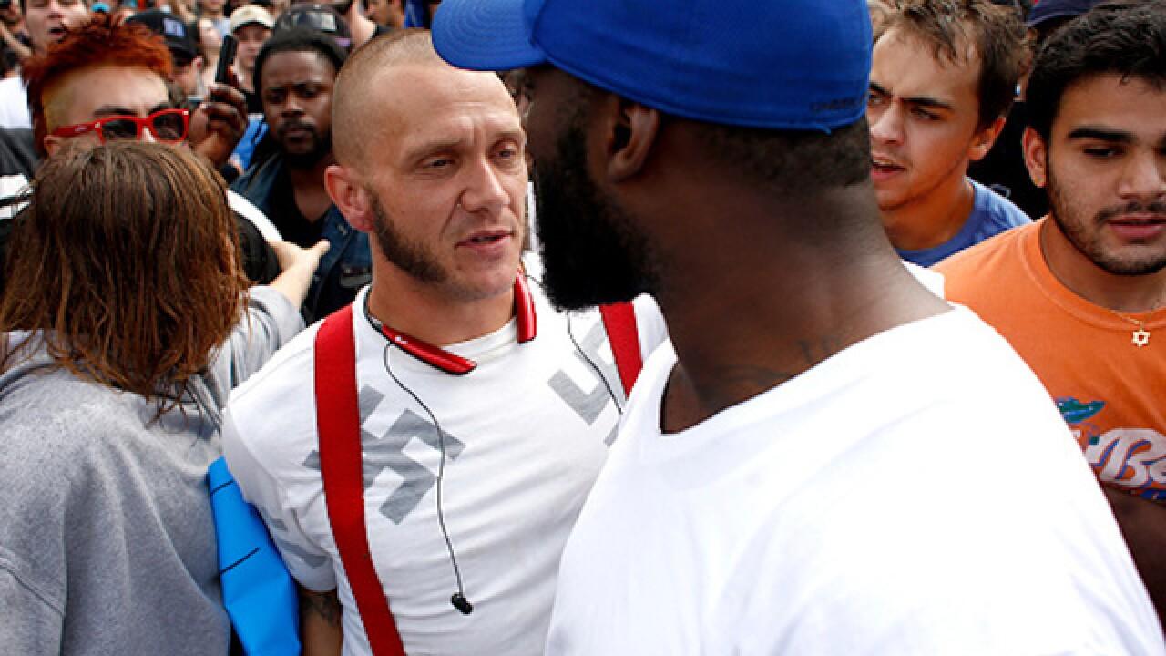 Black man hugs swastika-clad man