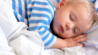 Boy with blond hair and blue and white pajamas takes nap