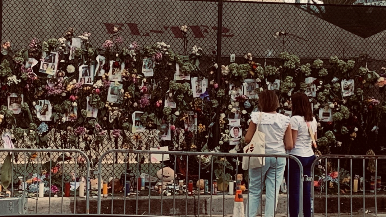 Women stare at makeshift memorial for Surfside condo collapse victims, June 29, 2021