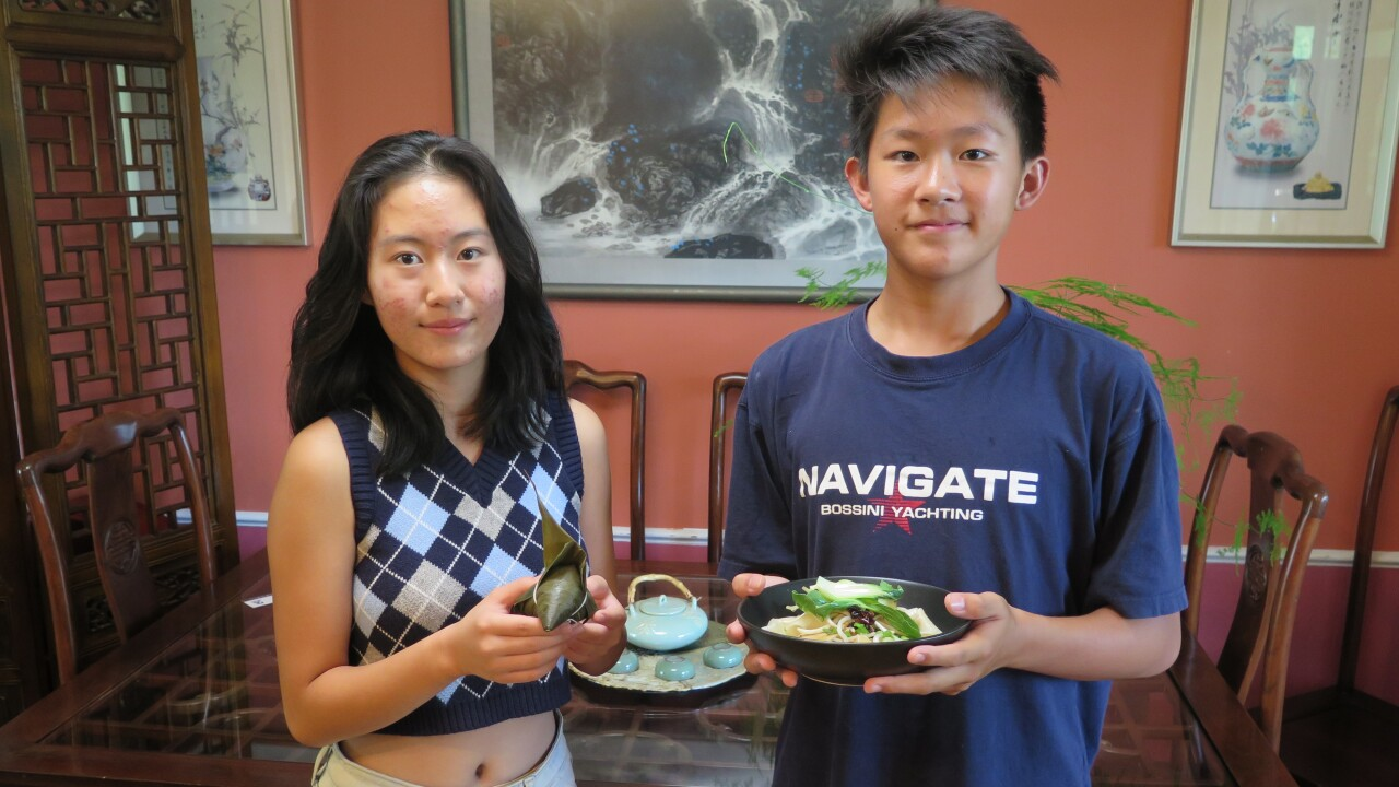 Katherine Wen, left, and Edward Zha hold the dishes they will be preparing for the 2021 Asian Food Fest Downtown. Katherine is holding Zongzi, a sticky rice dumpling. Edward is holding a bowl of Biang Biant Mian, a spicy noodle dish.