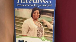 """A blue Donate Life Ohio poster reads, """"I'm alive because someone like you said yes!"""" above a photo of Loretta Davis posing for the camera wearing a beige sweater and a leopard-print top."""